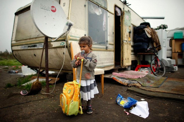 A girl leans on a school back pack outside a caravan at an encampment of Roma families in Triel-sur-Seine, near Paris